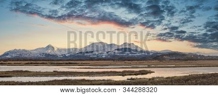 Majestic Landscape Image Of Snowdonia Snowcapped Mountains With Dramatic Sunset Clouds And Beautiful