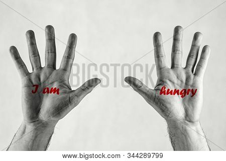 Male Hands In The Air With Red Lettering `i Am` `hungry`. Humanitarian Crisis Concept.male Hands In