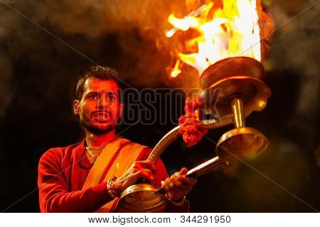 VARANASI, INDIA, JANUARY 17, 2019 : Portrait of Hindu priests waving fire cup during the Ganga Aarti ceremony along the river bank