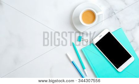 Feminine Workspace With Mint Paper Notebook, Cup Of Coffee, Office Supplies, Smartphone On Marble De