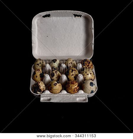 One Dozen Unwashed Quail Eggs In Open Carton Isolated On Black Background, Top View