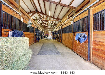 Horse Stable Interior With Hey And Wood Doors.
