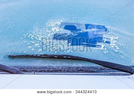 Teen driver in a car looking through a frost covered windshield shallow focus on windshield wipers