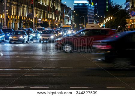 Car Traffic During Rush Hour At Night. Blurred Cars In Motion