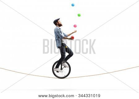 Full length profile shot of a bearded male hipster juggler with balls riding a unicycle on a rope isolated on white background