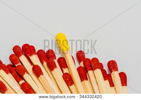One Single Yellow Tipped Matchstick Laying On Top Of Many Red Tipped Matchsticks