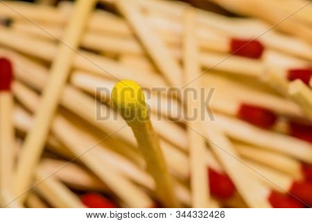 One Single Yellow Tipped Matchstick Standing In Middle Of Many Blurred Out Red Tipped Matchsticks