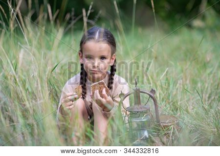 Pretty little girl with long pigtails and beautiful dirty face sitting at meadow with vintage paraffin stove and eating stale bread. Orphan, child of war, poverty, hunger, famine, poor destitute kid.