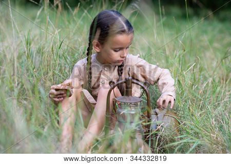 Pretty little girl with long pigtails and beautiful dirty face sitting at summer meadow with vintage paraffin stove and eating bread. Orphan, child of war, poverty, hunger, famine, poor destitute kid.