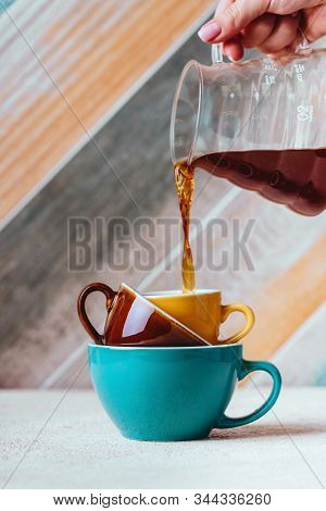 Woman Hand Pouring Coffee On A Cup On Colorfull Background