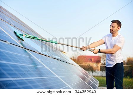 Young Man Is Washing A Solar Panel With A Mop, Pv Plant In Rural Area, Cleaning Increases To High Pe