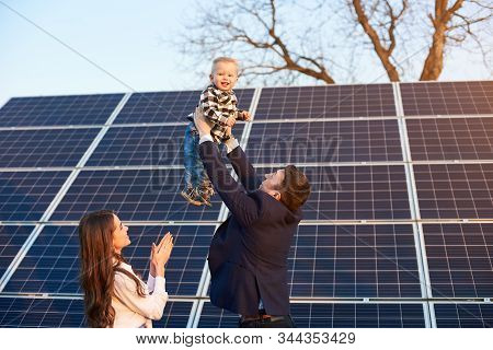 Low Angle View Of A Happy Family Spending Fun Time At Solar Plant, Father Holding His Son Above Thei