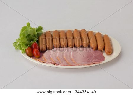 Smoked Sausages And Sliced Ham Served With Tomato And Vegetable On White Dish Isolated On White Back