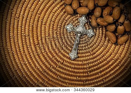 Close-up Of An Old Silver Crucifix With Jesus Christ And Wooden Rosary Bead On Brown Woven Wicker Te