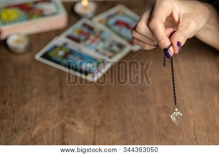 Arm Of Dowser With Hand-held Pendulum On The Background Of Tarot Cards. Selective Focus.