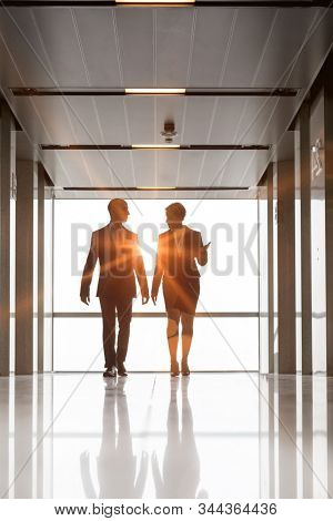 Business people walking while talking in office hall with yellow lens flare