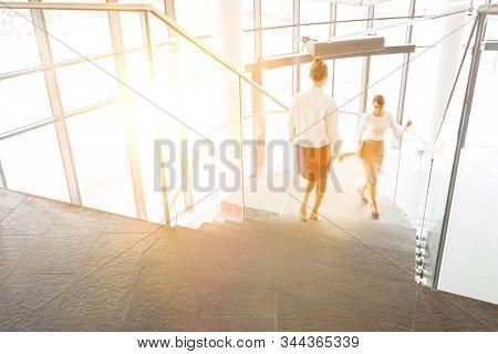 Businesswomen walking on staircase in office