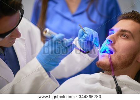 Dentist using dental LED curing light for polymerization of composite light-cure filling materials