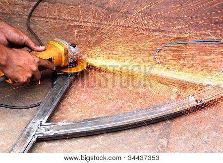 Mechanic Using A Electrically Operated Sawing Machine To Smooth The Rough Edges Of A Welded Iron Bar