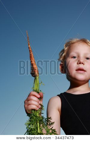 Young Child Holding A Carrot