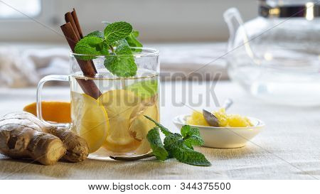 Ingredients For A Hot Tea With Lemon, Ginger, Mint And Honey In A Glass Cup.