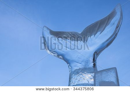 An Ice Sculpture Of A Tail Of Fish Against A Blue Sky Background. Copy Space