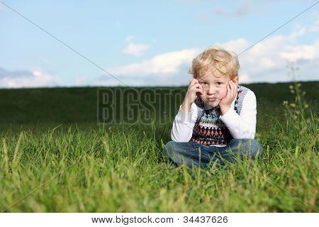 Glum Little Boy Sitting In Grass