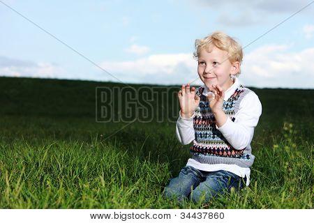 Impish Little Boy Kneeling In Green Field