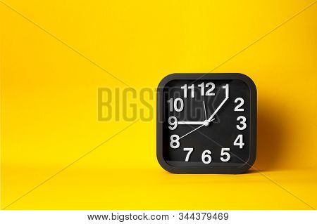 Black And White Clock Time Face On Yellow Background