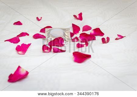 Condom And Rose Petal On The Bed.