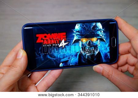 Ukraine, Berdyansk - December 24: Hands Hold The Phone With The Included Game Zombie Army 4.