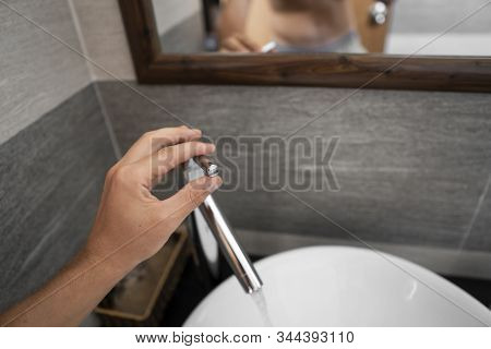 Male Hand Use A Faucet In A Bathroom Interior With White Round Sink And Chrome Faucet. Water Flowing
