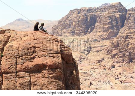 Petra, Jordan - March 28, 2019: Typical Bedouins Sitting On Rock At High Place Of Sacrifice In Ancie