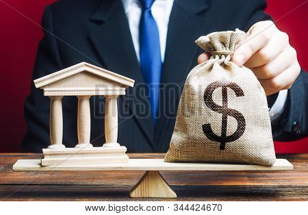 A Man Puts A Money Bag On Scales Opposite To Building Of Government, Bank, University. Budget And Fu