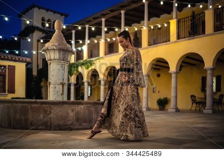 Lady in beautiful dress posing near fountain