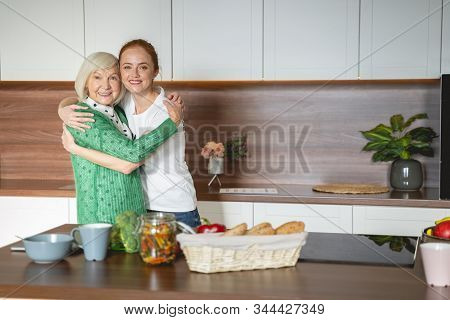 Cheerful Mature Woman Embracing Her Young Volunteer