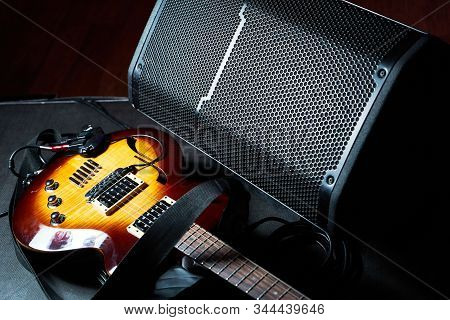 Yellow Electric Guitar And Black Amplifier On A Dark Background, Close-up