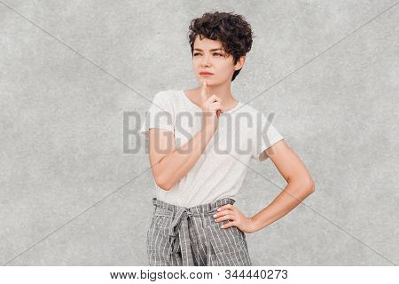 Charming Young Woman With Creative Hairstyle Is Posing With Intrigued And Thoughtful Face. Human Emo