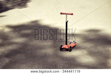 Children's Scooter Red Color On The Asphalt Road. Children's Scooter Left In The Shade Of Trees Forg