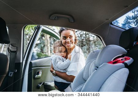 Smiling Mother Putting Baby Daughter In A Car Seat. Young Woman Holding A Child On Hands Near A Car.