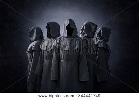 Group of five scary figures in hooded cloaks in the dark