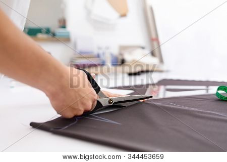 Young Female Dressmaker Cuts Dress Detail On The Sketch Lines With Scissors. Close-up View Fashion D