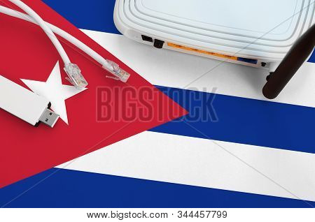 Cuba Flag Depicted On Table With Internet Rj45 Cable, Wireless Usb Wifi Adapter And Router. Internet