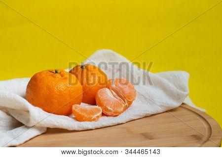 Mandarin And Slices Of Citrus On A Yellow Background. Orange Mandarin Or Tangerine Natural Fruit.