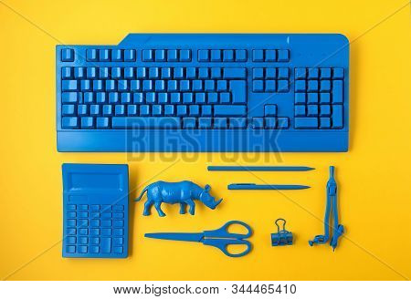 Office Suplies Painted In Classic Blue Color Over Yelow Background. Study, Education, Creative Offic