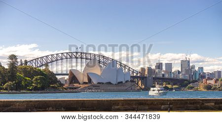 Sydney Opera House And Harbour Bridge With Boat And Buildings In Background On The Sunny Clear Sky D