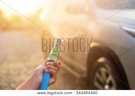 Happy Asian Little Boy Playing Water From Hose And Spray To Washing The Car At Outdoor In Morning Ti