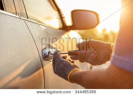 Car Technician Wearing White Gloves And Using Screwdriver To Fix, Repair Or Open The Door Of Modern