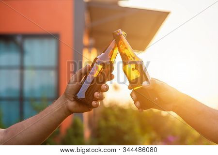 Close Up Two Of People Holding The Beer Bottle And Celebrate At The Outside Of The House. Moving To