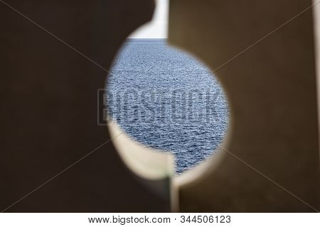 View Of The Mediterranean Sea From A Hole In A Railing